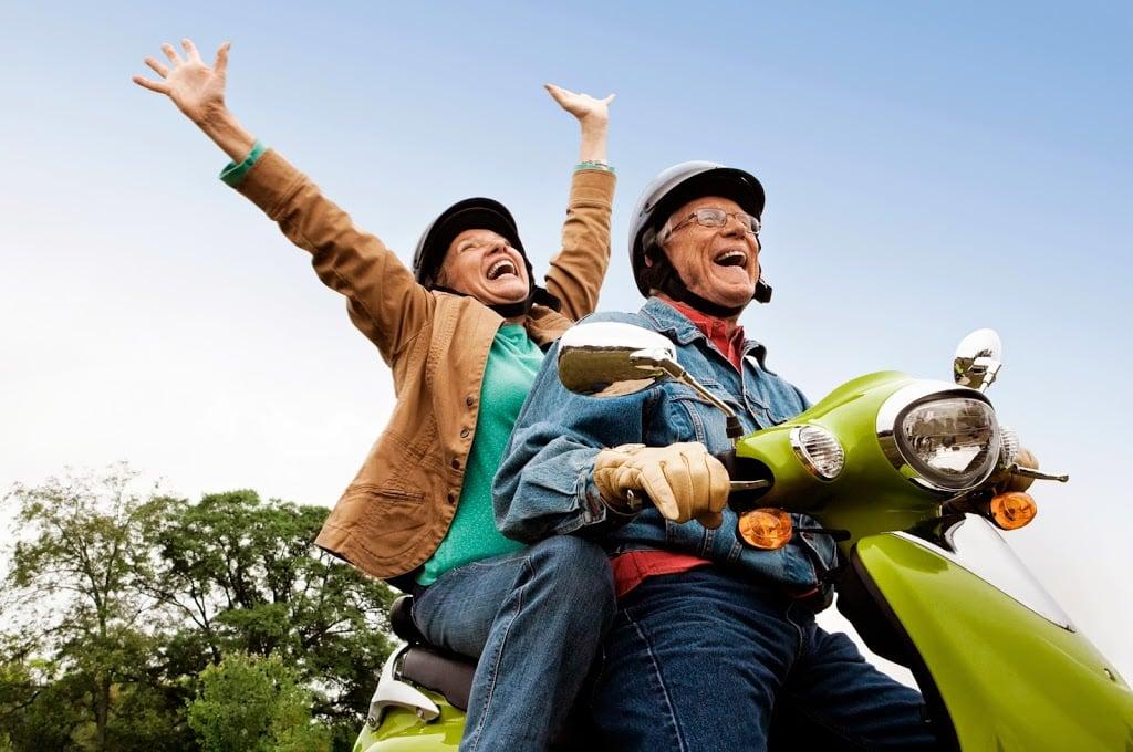 Senior couple having fun on moped