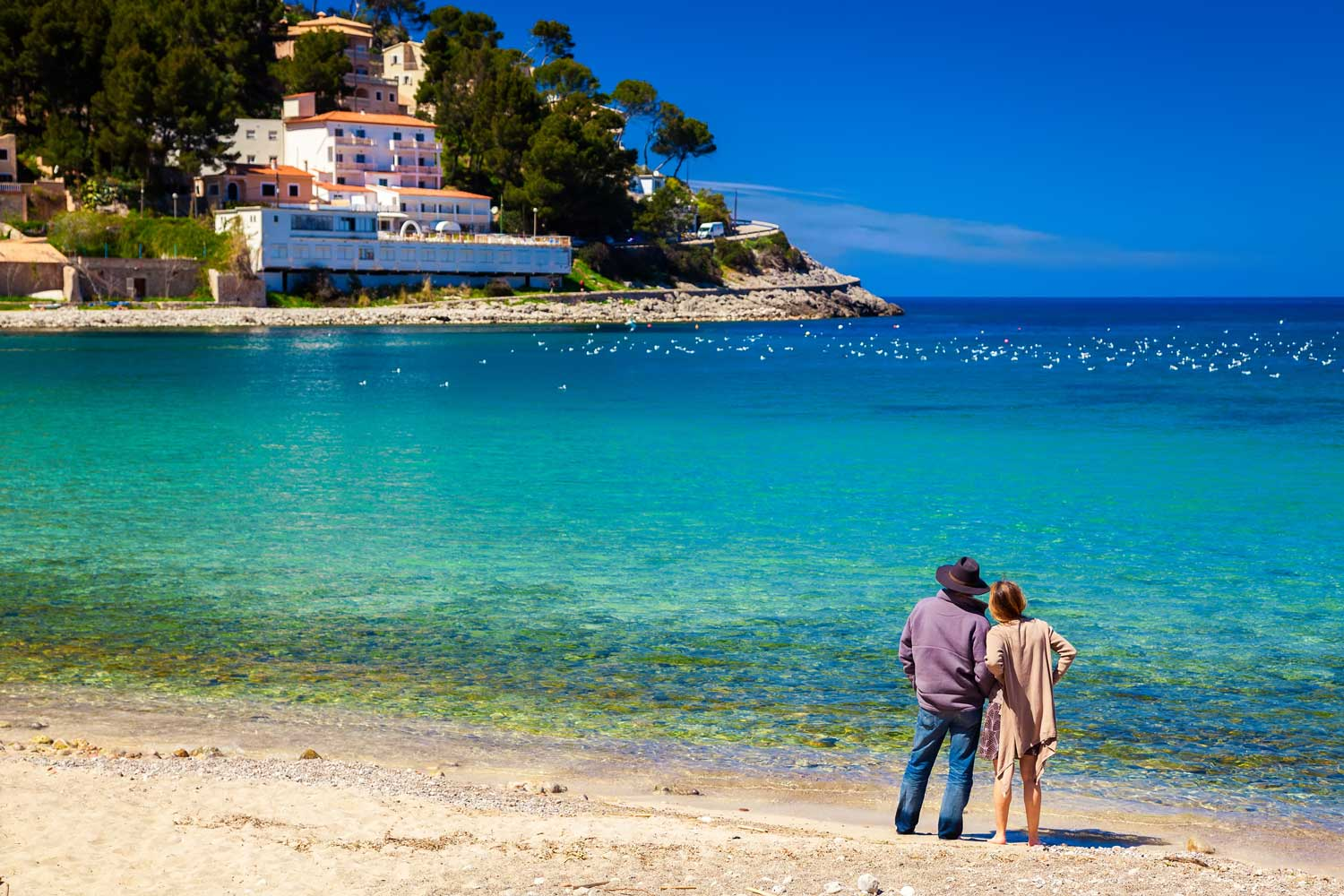 bigstock-Couple-Standing-At-The-Beach-98424761