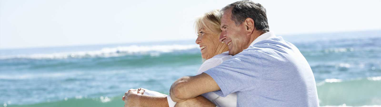 Senior couple sitting on the beach looking at the sea