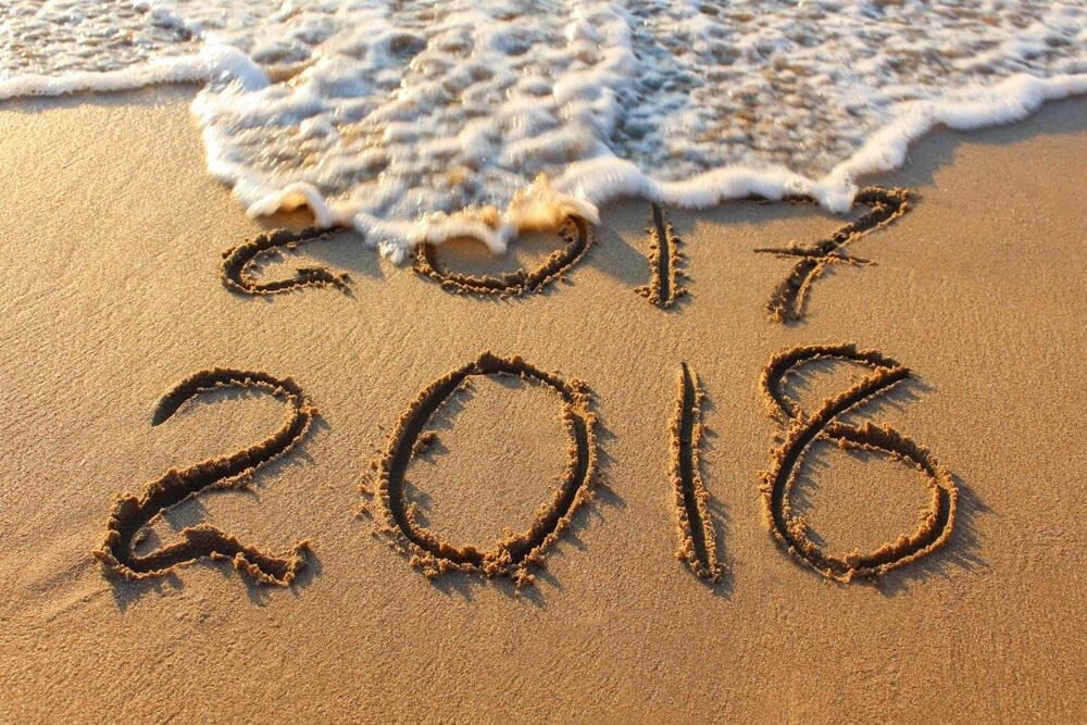 2018 year written on sandy beach sea. Inscription 2017 washes off wave.